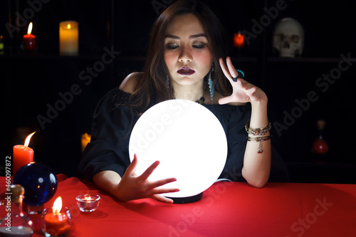 Obraz na plátně Mysterious magnificent beautiful woman fortune teller in black dress reading future on luminous crystal ball, dark witch casting a spell with magical ball