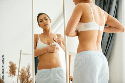 Young woman does breast self-examination while looking herself in mirror Fototapet
