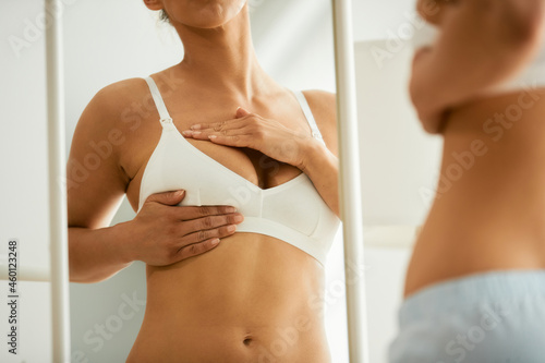 Canvas-taulu Close-up of woman does breast self-examination in front of mirror