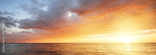 Baltic sea at sunset. Dramatic sky with glowing golden pink clouds, reflections in the water. Lighthouse. Setting sun. Epic seascape. Abstract natural pattern, texture, background, concept image