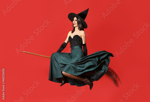 Obraz na plátně Young witch with broom on color background
