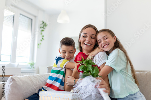 Foto Cheerful little girl with gift box and youngest brother with bouquet of roses flowers smiling and congratulating happy mom on mother day at home