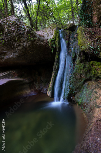 Fototapeta waterfall in the middle of the forest falling into a rocky natural pool, gorg de