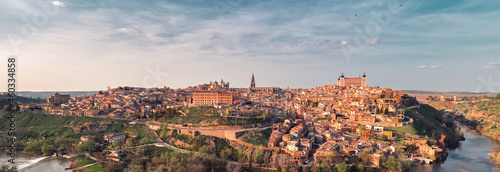 Fotografie, Obraz Distant panoramic view Toledo historical picturesque city surrounded by Tagus river located on hilltop, cloudy sky sunny day