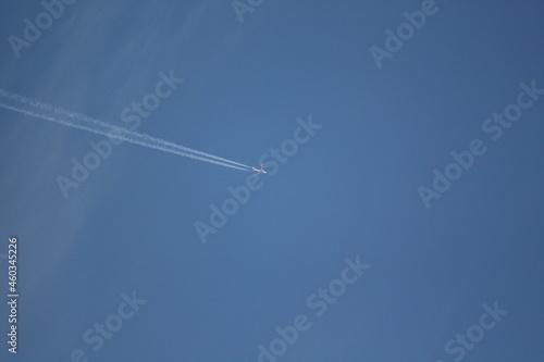 Flugzeug am blauen Himmel mit Kondensstreifen Fotobehang