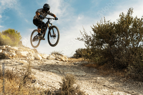 Canvastavla Professional bike rider jumping during downhill ride on his bicycle