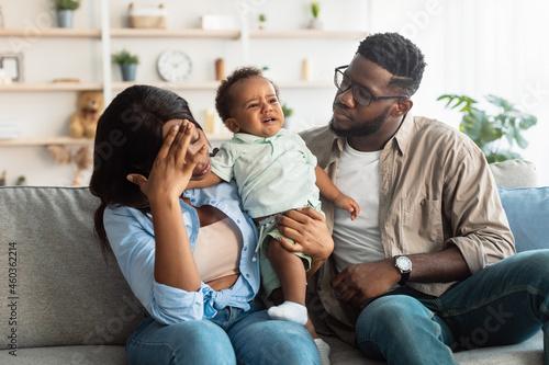 Billede på lærred Tired black parents sitting with crying kid on sofa