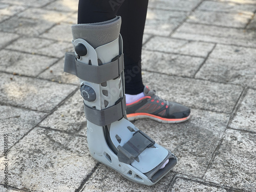 Photograph of orthopedic walking boots women with foot injury, fracture or sprained ankle Fototapet