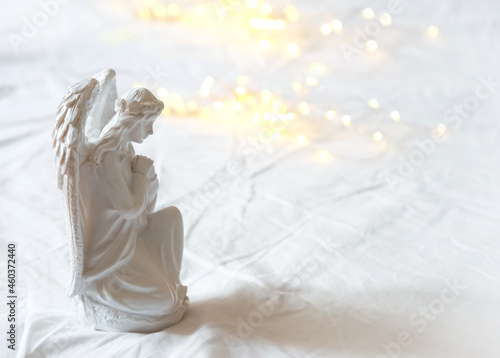 Canvas angel on white background with lights bokeh