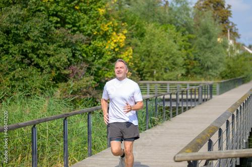Canvastavla Senior man jogging across a footbridge over wetlands