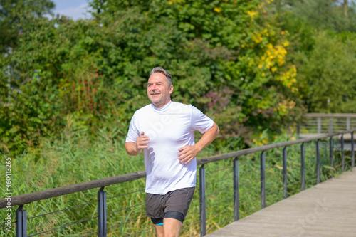 Senior man jogging across a footbridge over wetlands Fototapet