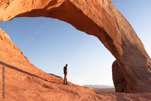 Fotografiet man hikig in arches national park at sunrise in moab utah