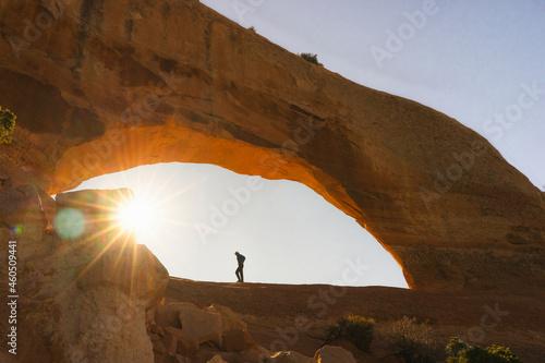 Tela hiker arches national park during sunrise