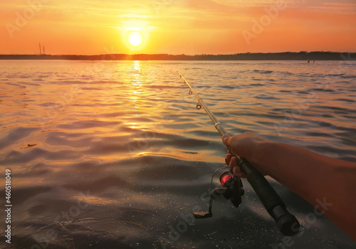 Fotografie, Obraz Close-up of a man's hand holding a fishing rod near the river at sunset, panorama of the water and the coast