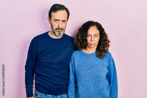Middle age couple of hispanic woman and man hugging and standing together depressed and worry for distress, crying angry and afraid Fototapet