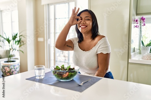 Tela Young hispanic woman eating healthy salad at home doing ok gesture with hand smiling, eye looking through fingers with happy face