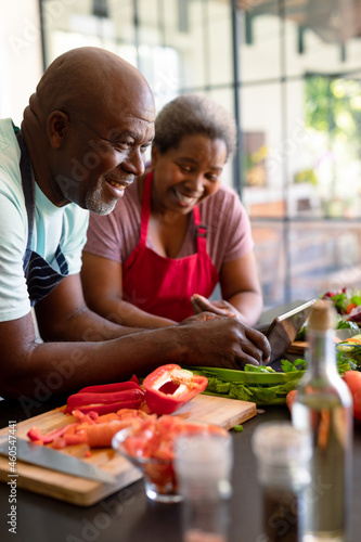 Happy african american senior couple cooking together in kitchen, using tablet