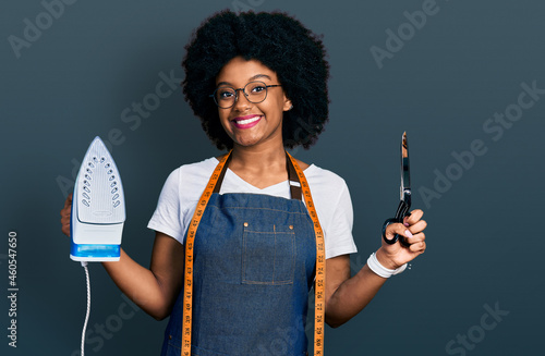 Foto Young african american woman dressmaker designer wearing atelier apron holding iron and scissors smiling with a happy and cool smile on face
