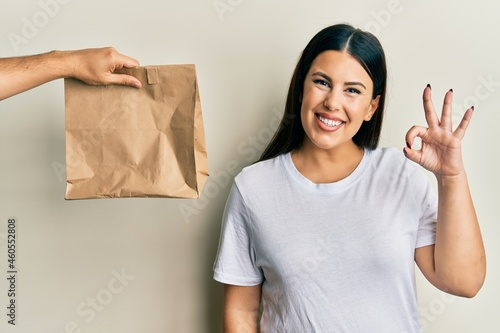 Murais de parede Beautiful brunette woman with take away paper bag doing ok sign with fingers, sm