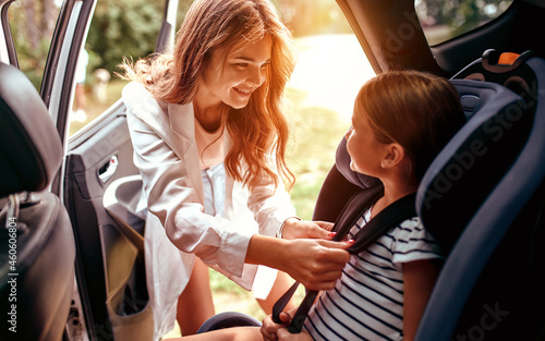 A cute woman mother put her daughter in a car seat and fastens her seat belts Fototapet