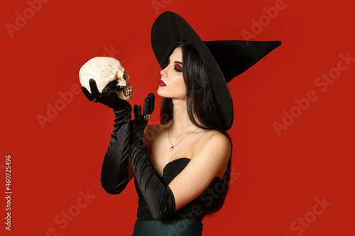 Fototapeta Young witch with human skull on color background