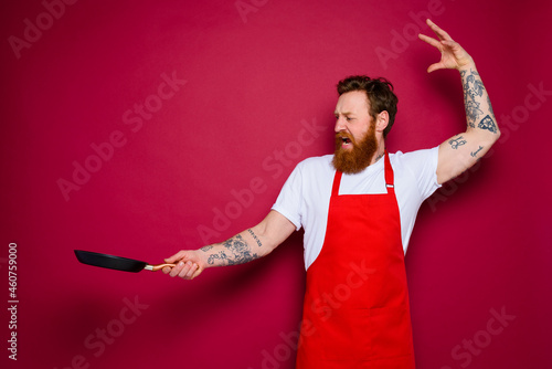 angry chef with beard and red apron cooks with pan Fototapet