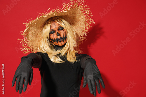 Young woman with Halloween makeup mask wearing straw hat black scarecrow costume raise hands close eyes like dead isolated on plain red background studio portrait Fototapeta