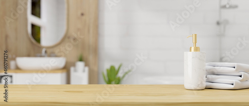 Fotografia Wooden table top with ceramic shampoo bottle and towels over bathroom interior b