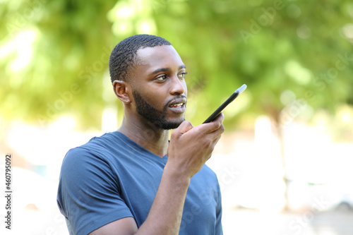 Foto Black man dictating audio message on smart phone