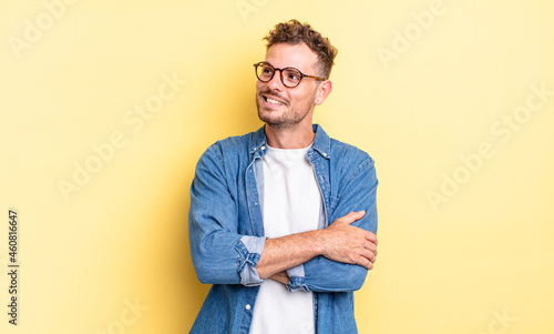 young handsome hispanic man feeling happy, proud and hopeful, wondering or thinking, looking up to copy space with crossed arms