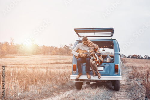 Fototapeta Handsome young man playing guitar for his girlfriend while both sitting in the c