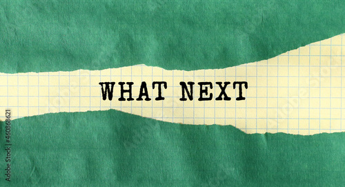 The WHAT NEXT message is written on a piece of paper. The inscription is readable under green torn paper.