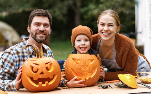 Fotografia Happy family parents and little boy son carving pumpkins in backyard