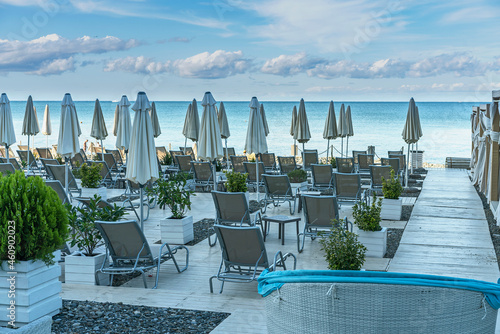 Fotografie, Obraz wooden ground on a pebble beach with sun loungers and umbrellas on the Black Sea