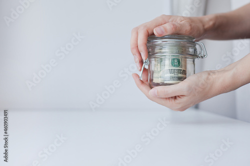 Fototapeta woman saving money in a glass jar
