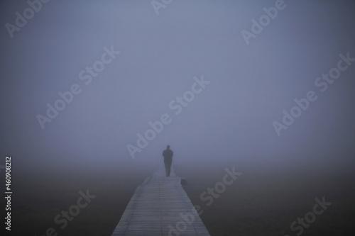 Fotografiet Person on wooden footbridge on a foggy day.