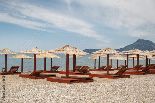 Obraz na plátně Beach with umbrellas and sun loungers by the sea on a sunny day, Montenegro