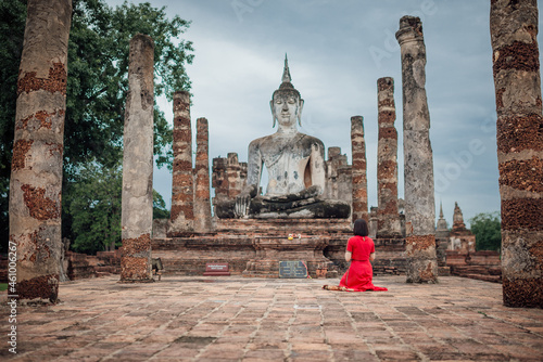 Photo The scenery of a woman with her Lanna-style umbrella praying in Wat Mahathat temple on a cloudy day in the rainy season at Sukhothai province, Thailand