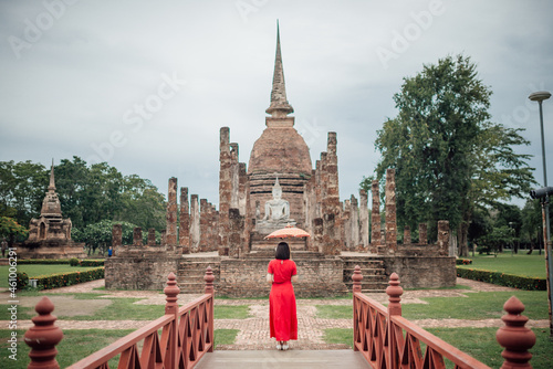 Obraz na plátně The scenery of a woman with her Lanna-style umbrella standing in front of Wat Mahathat temple on a cloudy day in the rainy season at Sukhothai province, Thailand
