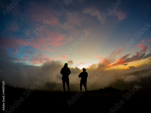 Fotografie, Obraz Silhouettes of two campers watching the sunrise in the mist from top of 'Le Pouc