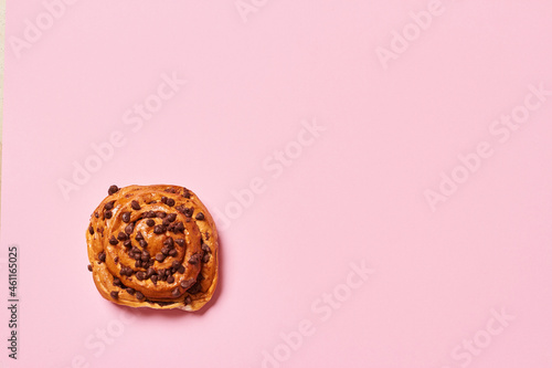 Obraz na plátně Sweet roll bread with chocolate chips isolated on pink background with copy space