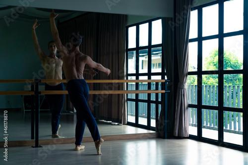 Tela Confidence Caucasian male ballet dancer practicing ballet dance alone in studio room