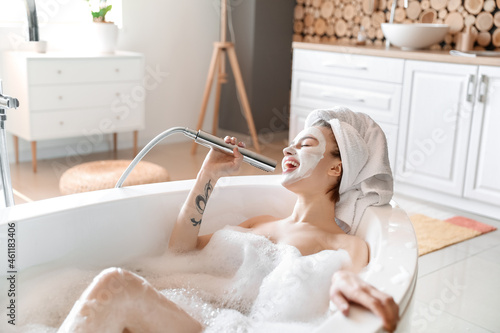 Fotografering Young woman singing while taking bath at home