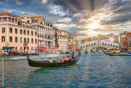 Venetian gondolier punting gondola through Grand canal waters of Venice Italy near Rialto bridge Fototapet