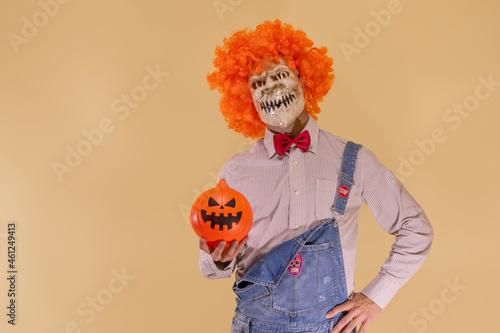 Fotografia, Obraz Payaso con peluca naranja sujetando la calabaza de Halloween, en fondo marrón con espacio para texto