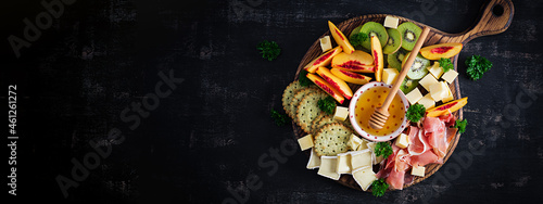 Fotografia, Obraz Italian antipasto catering platter with prosciutto, cheese and fruit on a dark background