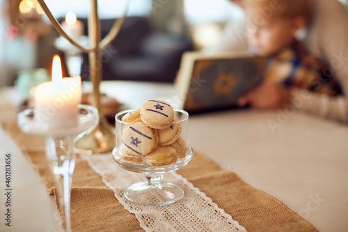 Billede på lærred Jewish cookies in jar with mother and son in background.