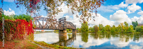 Panoramic view over an old railway metal rusty bridge in red ivy leaves over Elbe river in downtown of Magdeburg in Autumn colors and sunny day, Germany Fototapet