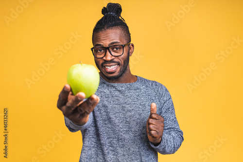 Canvas Healthy african american black man holding an apple isolated over yellow background