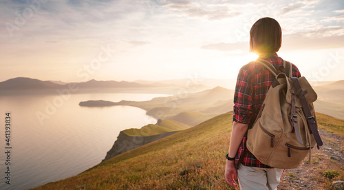 Fotografie, Obraz A young Asian woman with a backpack hiking in the summer and enjoying the view of the sunset sea and mountains